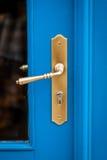 Brass door handle on a colorful blue door Royalty Free Stock Photos