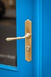 Brass door handle on a colorful blue door Stock Photo