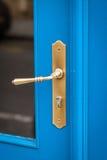 Brass door handle on a colorful blue door Stock Photo