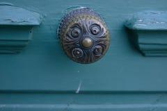 Brass door knob handle on turquoise door peeling paint style vintage antique travel stock image