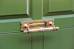 Brass door knocker letter box. Photo of a vintage brass door knocker letter box on green door Stock Images