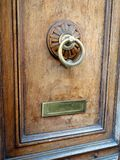 Polished Brass Door Knocker, Rome, Italy. A brass door knocker polished through use, and a patinated brass letter or mail slot, on a wooden door showing grain Royalty Free Stock Image