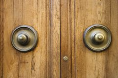 Brass doorknobs on wooden door. Royalty Free Stock Photography