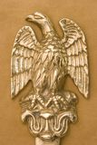 Brass Eagle. The brass eagle of an antique letter opener on tan suede background royalty free stock photo
