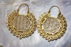 Brass earrings in boho style. On mother pearl background royalty free stock image