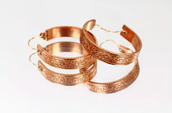 Brass earrings on mirrored surface Royalty Free Stock Photo