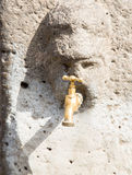 Brass Faucet in Pompeii Stone Face. Ancient Stone face in Pompeii with brass faucet royalty free stock images