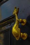 Brass fish knocker, knocker on black wooden door, decorative ele Stock Photo