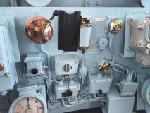 Ship& x27;s Gauges. Brass fittings and gauges in this old ship stand out against the pale blue paint Stock Photo