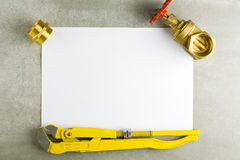 Brass fittings on sheet of paper. Royalty Free Stock Image