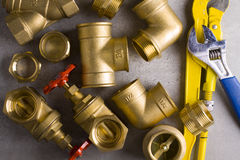 Brass fittings with wrench. Brass nipple in yellow wrench on grey background Stock Photos