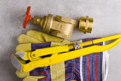 Brass fittings with wrench. Brass nipple in yellow wrench on grey background Royalty Free Stock Image