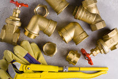 Brass fittings with wrench. Yellow brass fittings and gate valve background Royalty Free Stock Photos