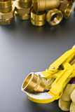 Brass fittings with wrench. Yellow brass fittings and gate valve background Royalty Free Stock Image