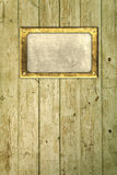 Brass frame on floorboards. Brass nameplate on distressed floorboards stock image