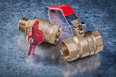 Brass gate lever ball valve on scratched metallic background plu Royalty Free Stock Photo