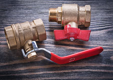 Brass gate lever ball valves on wooden background plumbing conce Stock Photos