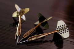 Brass Gold Darts on Brown Table Royalty Free Stock Image