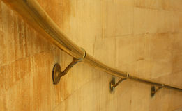 Brass handrail. Curving brass handrail attached to a stone wall Royalty Free Stock Photos