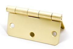 Brass Hinge. A macro shot of a brass hinge over a white background stock photo