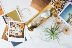 Brass Hourglass with polaroids and air plant stock photo