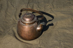 Brass Kettle. On the raincoat-tent Stock Images