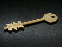 Brass  key on black leather Stock Photos