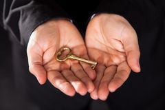 Brass key in cupped male hands Stock Image