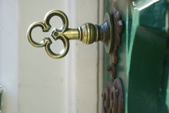 Brass key in a green old door Stock Photography