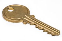 Brass key on isolated white background. Yellow brass key on isolated white background Stock Images