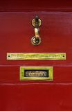 Brass Knocker on red door. A brass door knocker and letterbox on a red gloss painted wooden door Stock Image