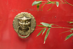 The brass knocker on the red door and green bamboo Stock Photography