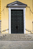 Brass   knocker and wood  door in a church   gallarate  italy. Brass brown knocker and wood  door in a church crenna gallarate varese italy Royalty Free Stock Photo