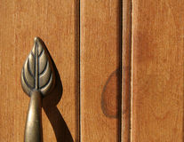 Brass Leaf on Beadboard. Brass handle on beadboard door. Simulated odessa pine finish Stock Images