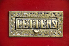 Brass Letter Box. A Brass Letter Box, quite ornate, set in to a painted red, wooden door royalty free stock image