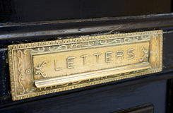 Brass letterbox slot  in old door Stock Photos