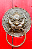 Brass Lion Door Knocker. Oriental brass lion head door knocker on red wooden door Stock Image