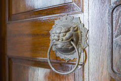 Brass lion head door knocker on wooden door Stock Photography