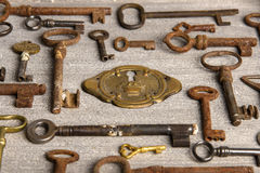 Brass lock surrounded by rusty antiques keys. Stock Photo Royalty Free Stock Photography