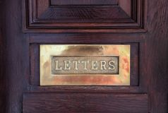Brass mail letter box on a wooden front door, text letters stock image