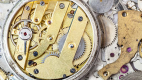 Brass mechanical watch on heap of spare parts Royalty Free Stock Photo