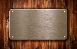 Brass metal plate on wooden background Stock Photo