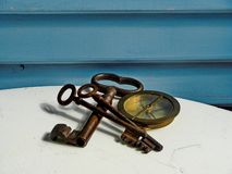 Brass navy compass and iron vintage keys on white and blue background. stock photos