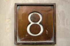 Brass number eight. Number eight cast in brass on the outside wall of a building in central London Royalty Free Stock Images