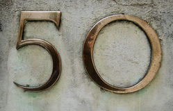 Brass number fifty. Brass figures for a number fifty outside an office block in central London Stock Images