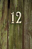 Brass number twelve on door Stock Photo