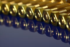 Brass nuts and bolts. Photograph of brass nuts and bolts reflected on a blue background Stock Photography