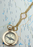 Brass old compass with chain on the map Stock Photography