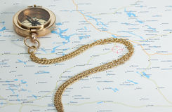 Brass old compass with chain on the map Royalty Free Stock Photo