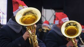 Brass orchestra in funny hats playing Christmas carols creating holiday spirit. Stock footage stock video footage